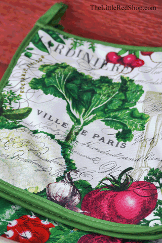 Detail of From My Garden Kitchen Potholder featuring tomatoes, cauliflower, radishes, peas, and other vegetables