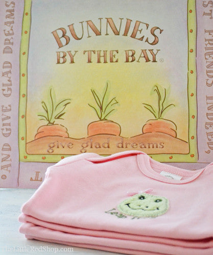 A folded stack of Bunnies by the Bay's Pink Lily Mae Leap Frog Bunsie Baby Onesie