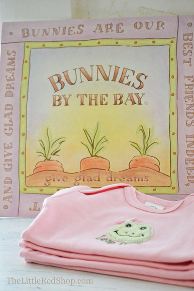 A folded stack of Bunnies by the Bay's Pink Lily Mae Leap Frog Bunsie Baby Onesie in front of Carrot Logo