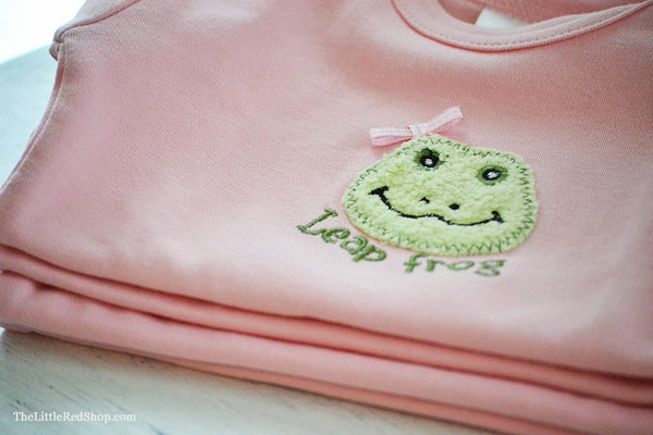 Close up of a A folded stack of Bunnies by the Bay's Pink Lily Mae Leap Frog Bunsie Baby Onesie