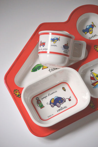 Red-trimmed Baby Cie Baby Travel-themed Dish set featuring planes, trains, and automobiles