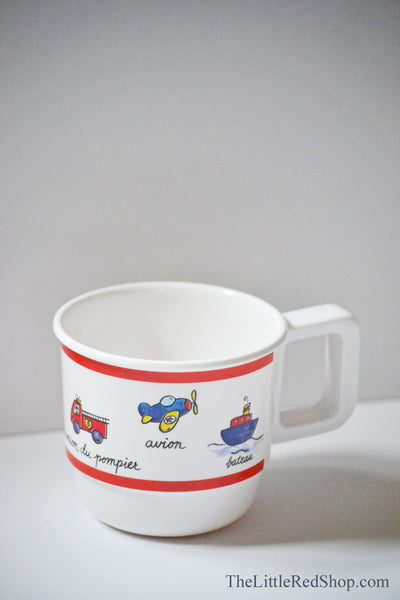 Baby Cie Baby Travel-themed cup featuring planes, trains, boats, and automobiles
