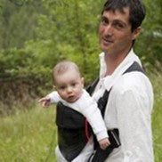 father with baby in outwards facing baby carrier