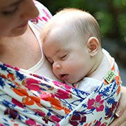 baby sleeping on mom in a wildflower boba baby wrap