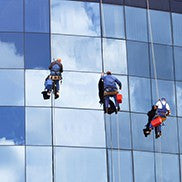 window washers hanging outside of a tall building
