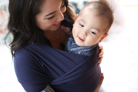 happy baby in a navy blue boba baby wrap carrier