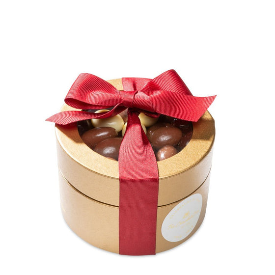 Assorted chocolate almonds in gold round box with red ribbon for Christmas