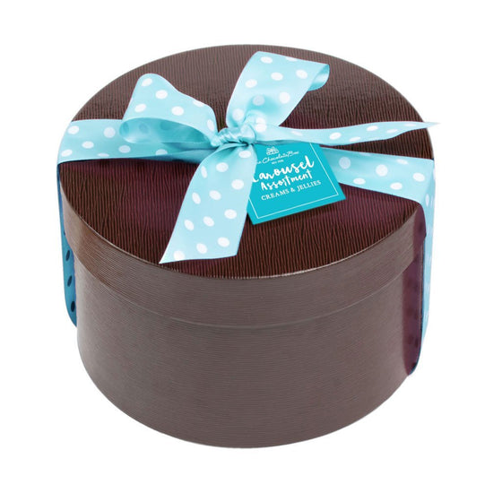 1kg Carousel Chocolate Assortment in brown leatherette round box with blue ribbon with white spots