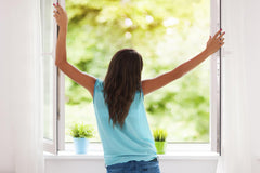Image of a girl standing in front of an open window looking out onto some green trees