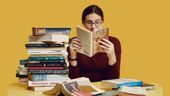 Image of a woman reading a book and surrounded by a pile of books
