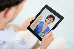 Image of a man with a tablet talking with a woman over video chat