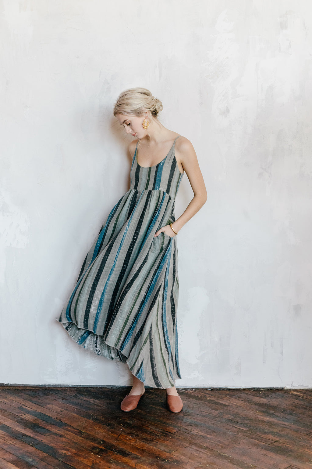 Model wearing a cotton gauze maxi dress in rose ash stripe. The dress cinches at the waist, has a smocked back and pockets.