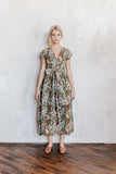 Model wearing an olive floral wrap dress made of a cotton/linen blend. The dress features embroidery details on the shoulder and earthly shades in the floral print.