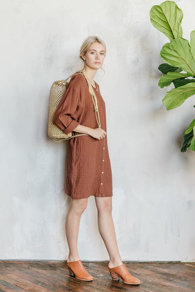 Model wearing an oversized sumac colored cotton gauze shirtdress.