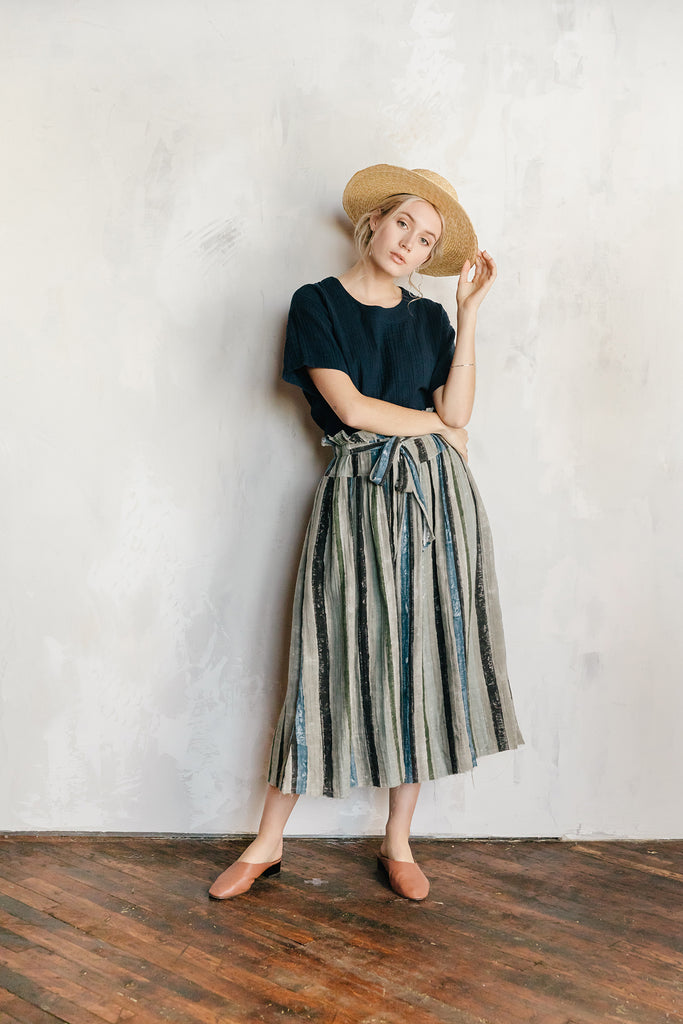 Model wearing 100% cotton pants featuring an elastic waist with a tie front. The pants have a wide leg and are shown in rose ash stripe.