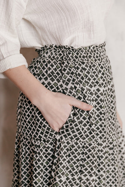 Model wearing a black and white geo print cotton/silk tiered midi skirt paired with a white 100% cotton double gauze top.