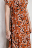 Model wearing an umber orange floral print ruffled tiered dress made of 100% cotton double gauze with a rolled sleeve.