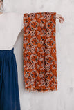 Model holding an umber orange floral print block scarf made of 100% cotton.