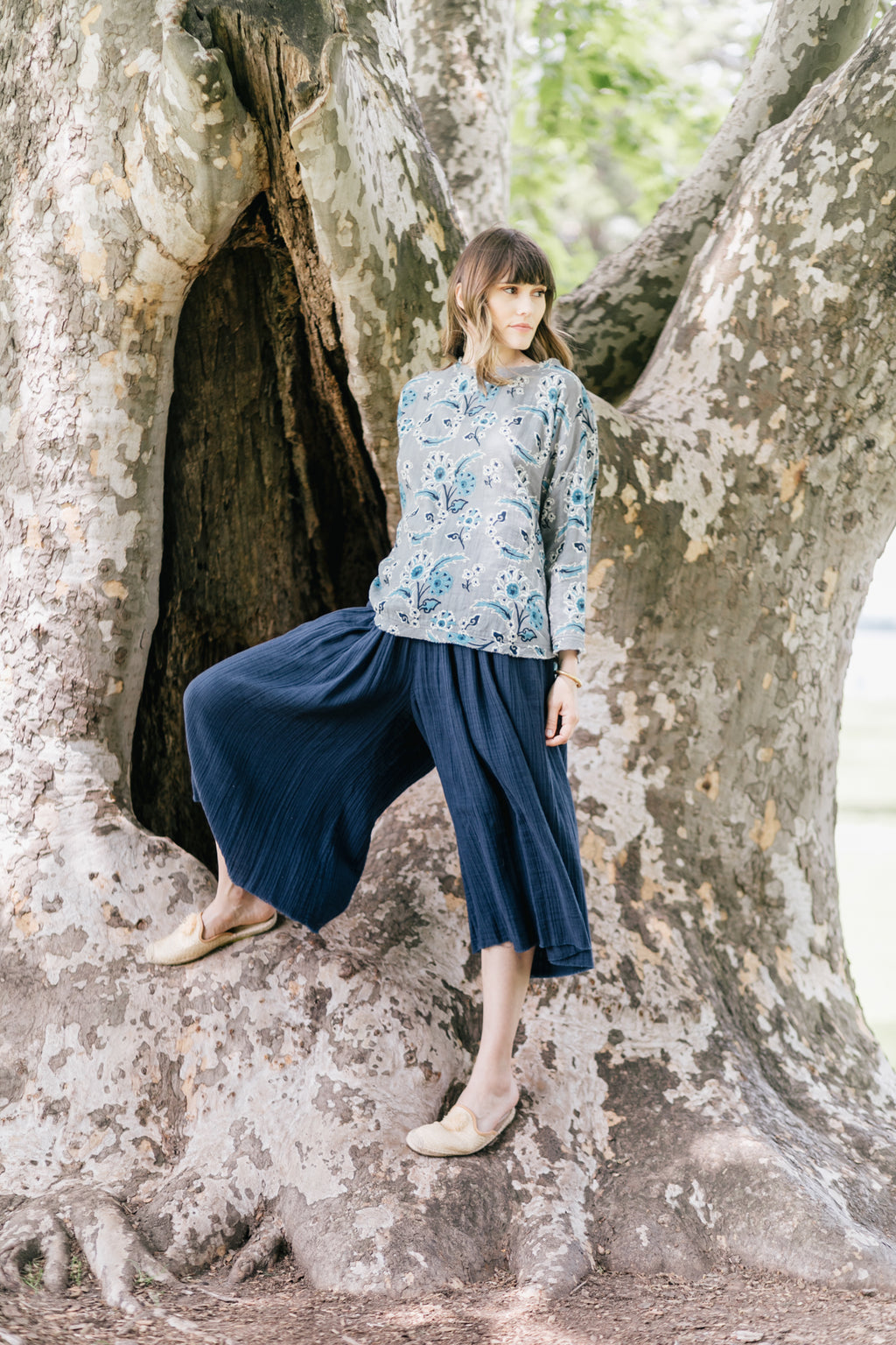Model wearing an indigo blue floral print top with a high low hem and cotton rolled sleeves paired with wide legged blue palazzo pants.