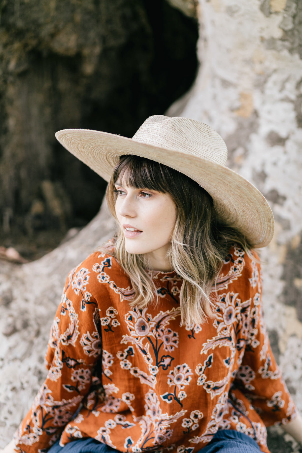 Model wearing an umber orange floral print top with a high low hem and cotton rolled sleeves paired with a wide brim straw hat.