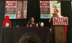 "Amber Crotty, Navajo Nation Delegate delivers Keynote ""We Carry Our Medicine"" supported by Cherrah Giles, Board Chairwoman of National Indigenous Women's Resource Center (seated)."