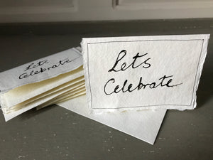 Handwritten LETS CELEBRATE cards with matching envelopes on handmade paper.