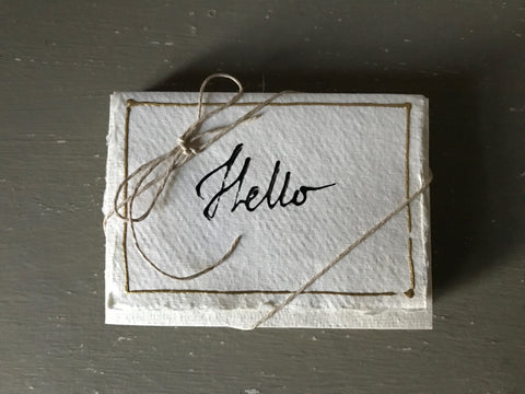Handwritten HELLO message cards with matching envelopes on handmade paper.