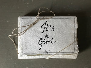 Handwritten IT'S A GIRL cards with matching envelopes on handmade paper.