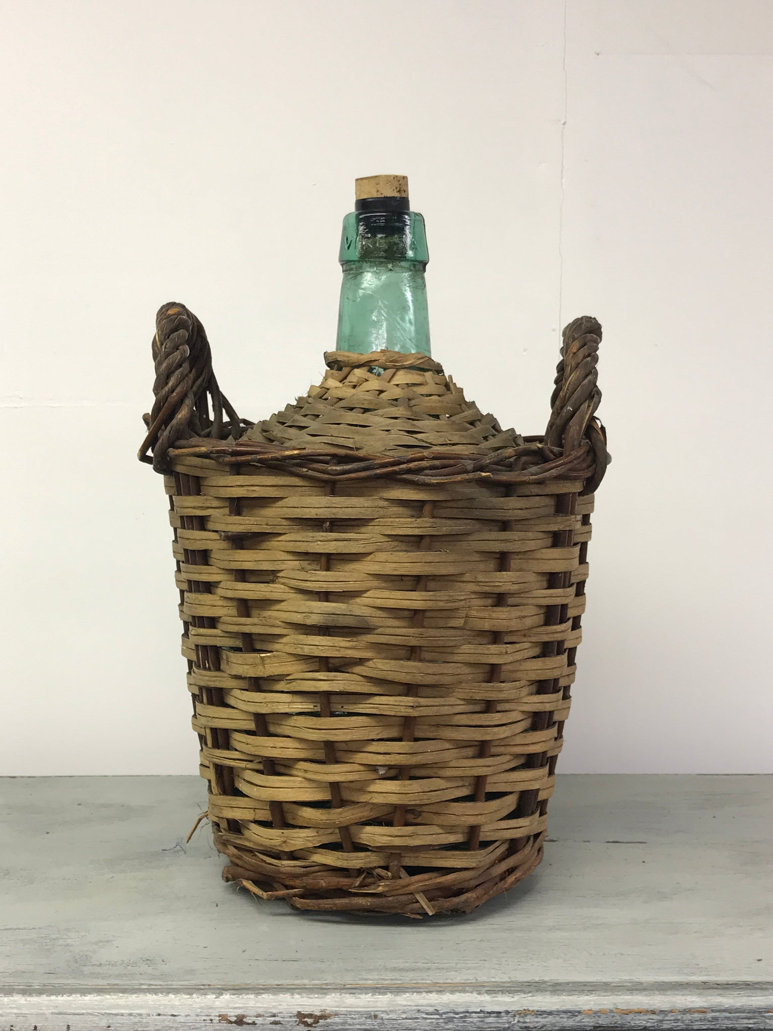 Early 20th century green glass Demi John in original basket