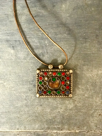 Antique Afghan Kuchi tribal pendant on leather cord.