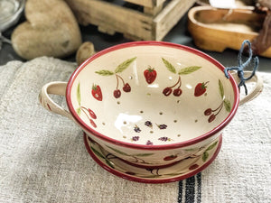 Handmade and decorated ceramic colander and plate.
