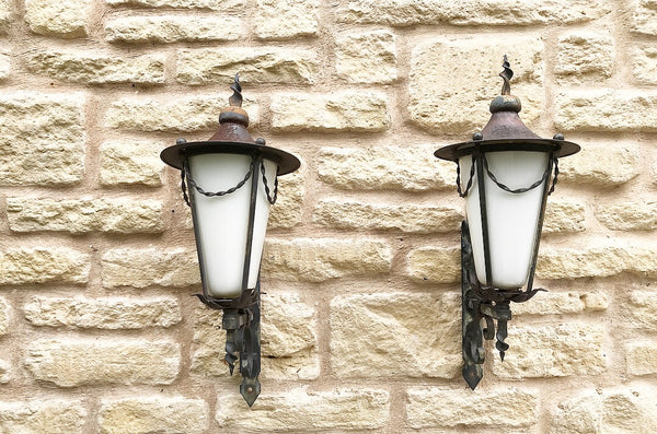 Early 20th century handmade wrought iron lanterns with original milky glass.