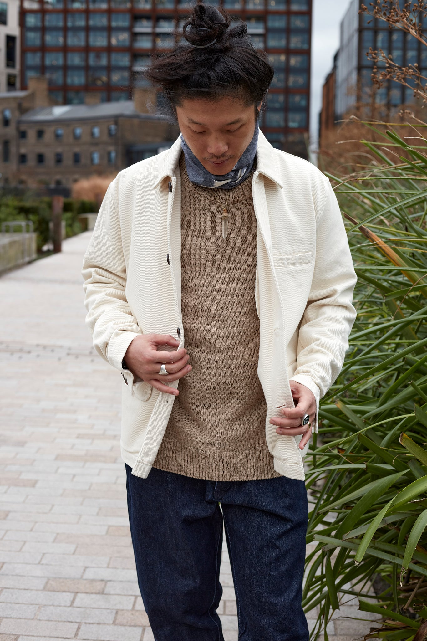 Model wears Universal Works Warmus Jacket with an Ikat Neckerchief and an Elm Loose Crew knit jumper.