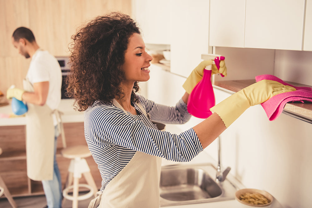 Woman cleaning kitchen cabinet with pink tower and pink spray bottle.