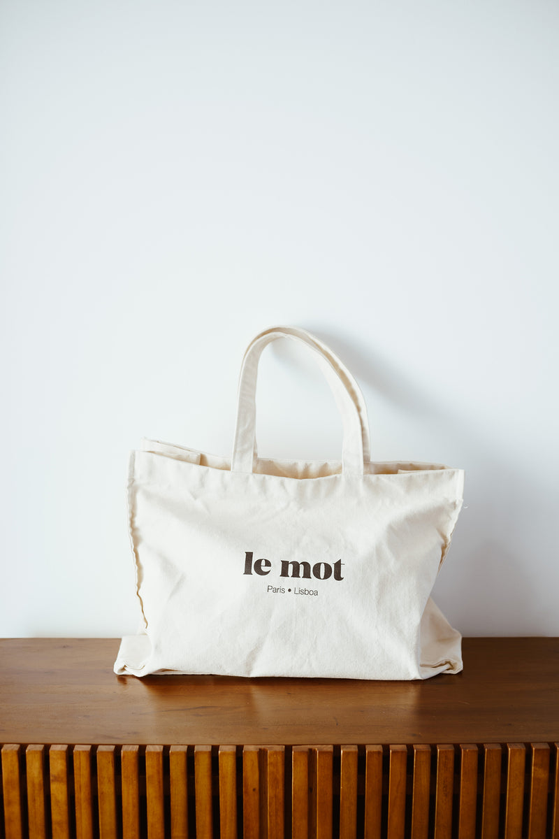 With its large size and thick cotton canvas, Le Tote can carry everything you might need. This piece is super versatile, perfect for every occasion, from going to the beach to your grocery run! With the Le Mot logo printed in black, Le Tote has the coolest and chic vibe of all tote bags.  100% Cotton Canvas 350grs  Made in Portugal  Measurements:  Bag - Width 54 cm  x  Height 42 cm Strap - 58 cm
