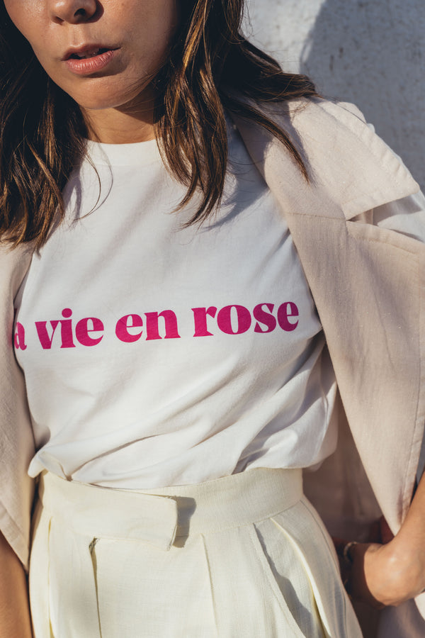 For Summer 2020, we reissued one of our absolute best sellers, the la vie en rose tee, that brings a touch of pink to your life! This time, we opted for our signature off white with a contrasting fucshia print, that reminds us of sunset tones and happy, hot Summer days. Full of love and emotion, this t-shirt is inspired by the famous Edith Piaf song and it's made for all the hopeless romantics out there.