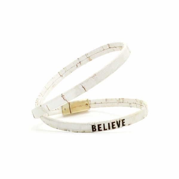 Believe bracelet made of thin white cork with a gold magnetic clasp.