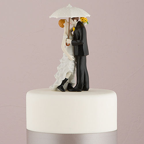 a romantic cake topper of a bride and groom with an umbrella