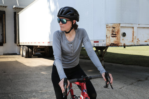 Woman wearing a Lory Merino Top riding a bicycle