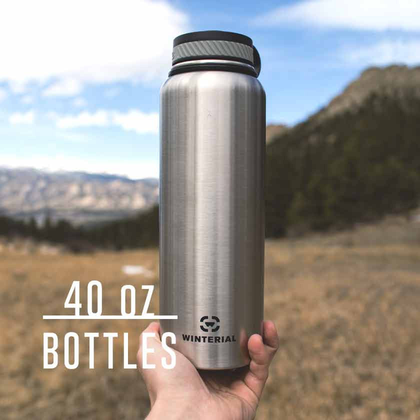 guy holding insulated water bottle up with mountains and valley in the background