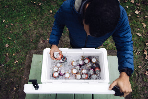 Man opening driftsun ice chest full of ice and beer on fall afternoon