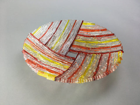 "Red, orange, yellow, and clear 9"" diameter fused glass bowl"