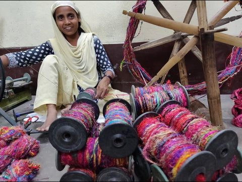 Woman spinning recycled sari yarn