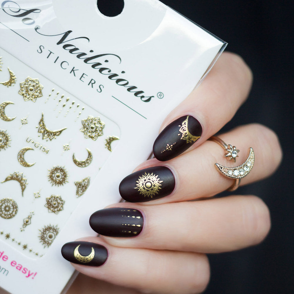 dark red nails with celestial stickers