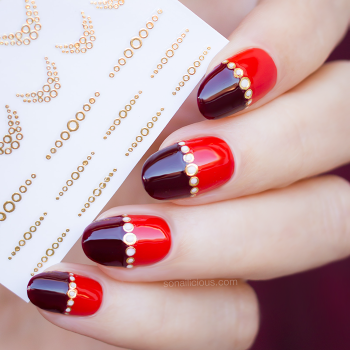 gold and red nails with gold nail stickers