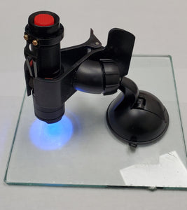 uv curing flashlight in suction holder mounted on a glass pane