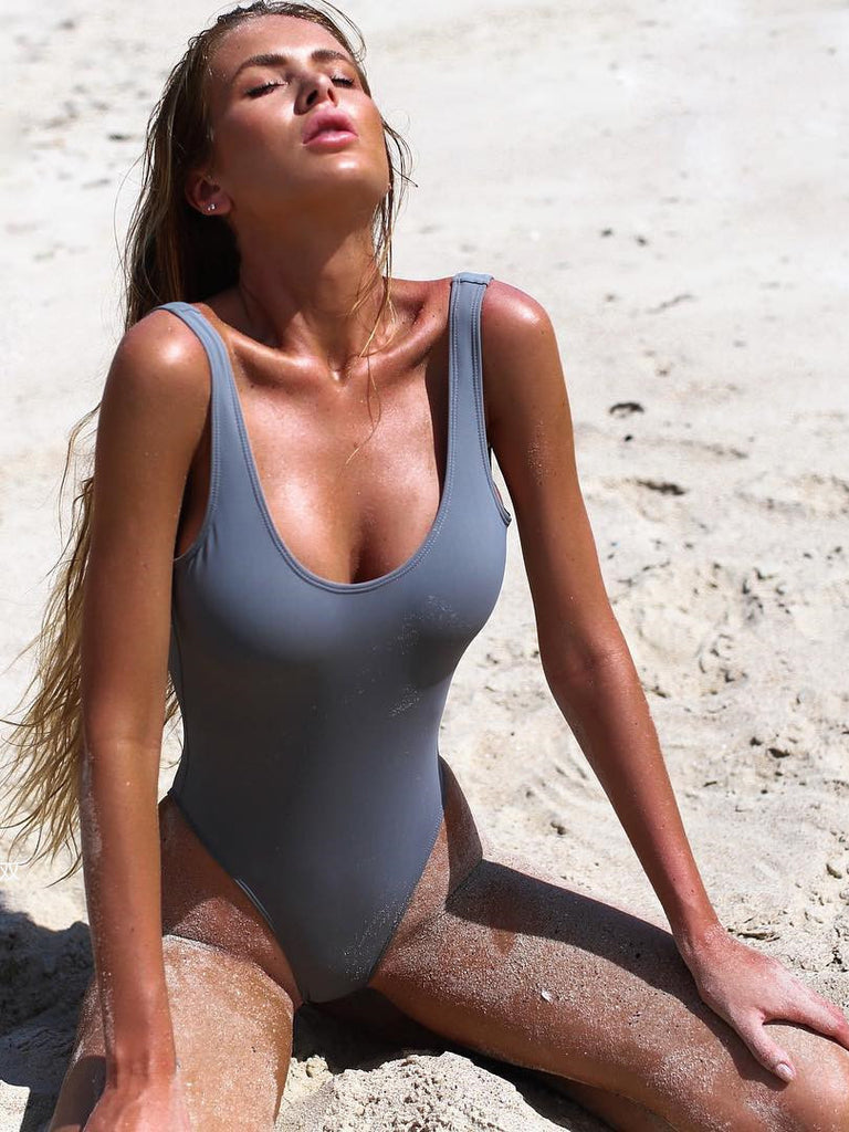 Classic solid one-piece swimsuit featuring a scoop neckline and a flirty low-back design