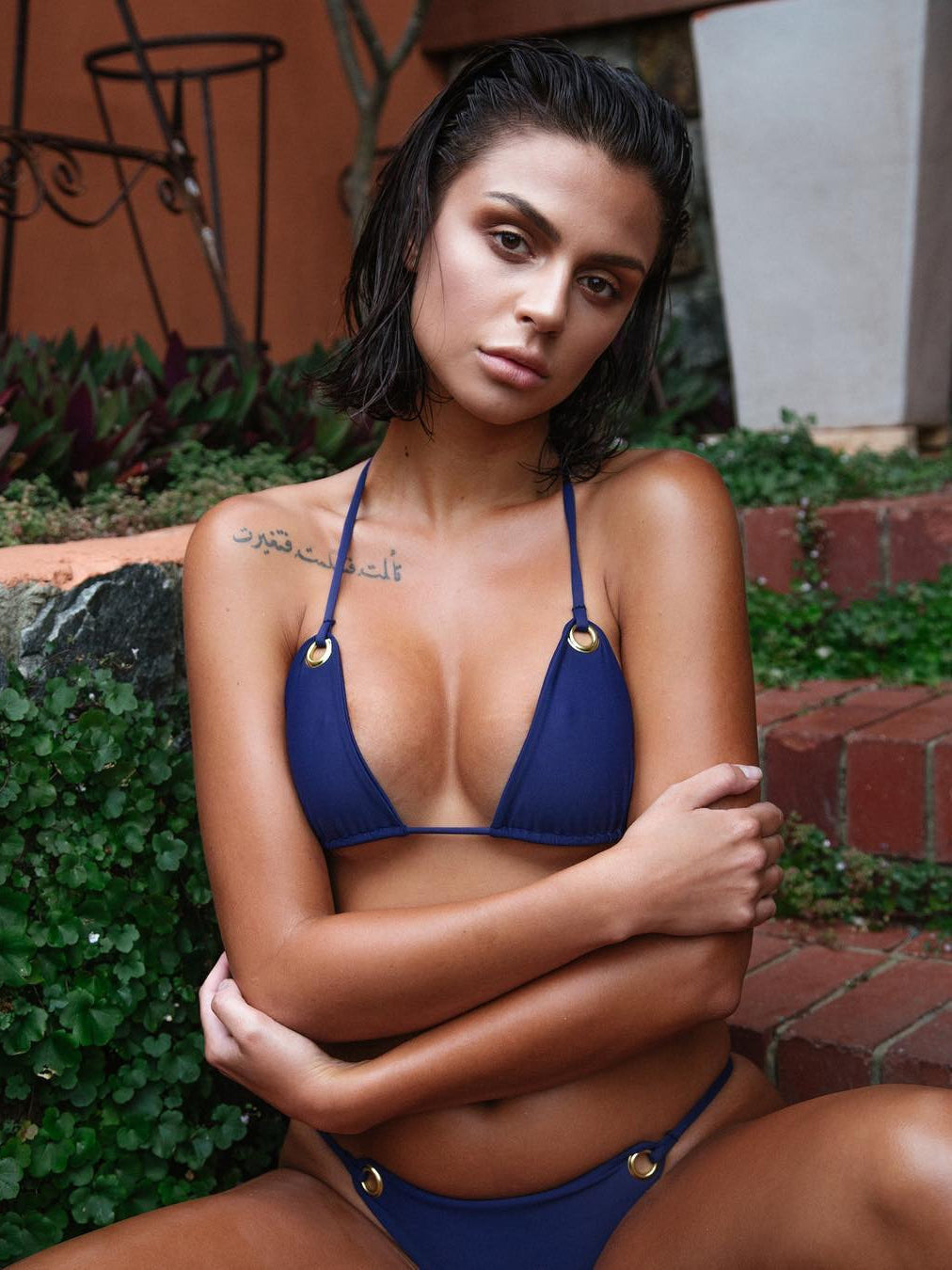 Solid bikini top featured in a triangle shape and high-polish grommet details