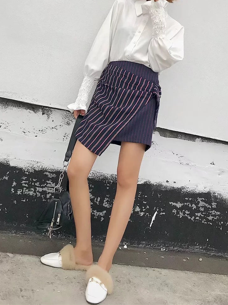 Striped and pleated, this mini skirt features an asymmetrical hemline and high-polish grommet detailing.
