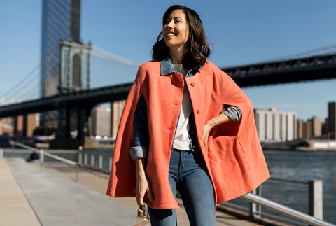 Coral cape over denim outfit